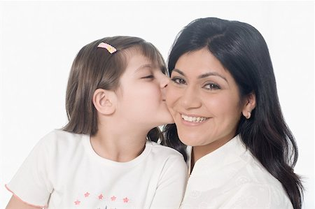 Close-up of a girl kissing her mother and smiling Stock Photo - Premium Royalty-Free, Code: 630-01877489