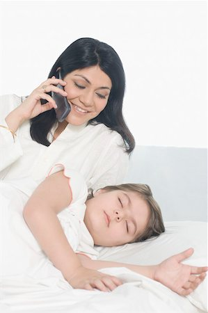 Girl sleeping on the bed with her mother talking on a mobile phone beside her Stock Photo - Premium Royalty-Free, Code: 630-01877494