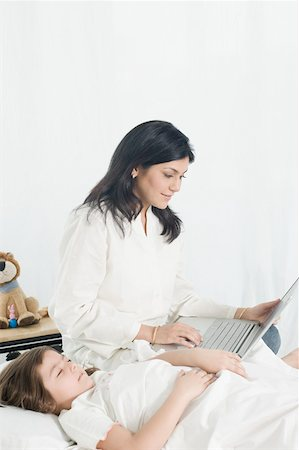 Mid adult woman using a laptop beside her daughter lying on the bed Stock Photo - Premium Royalty-Free, Code: 630-01877492