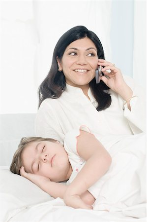 Mid adult woman talking on a mobile phone with her daughter sleeping beside her on the bed Stock Photo - Premium Royalty-Free, Code: 630-01877493