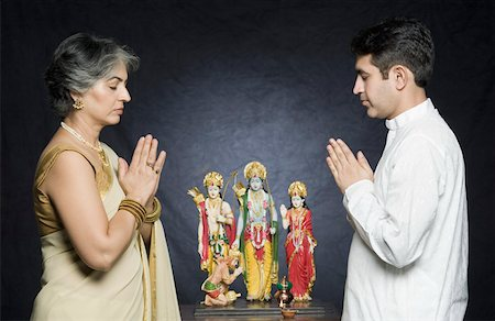 Side profile of a mature woman with her son praying in front of statues of God Stock Photo - Premium Royalty-Free, Code: 630-01877585