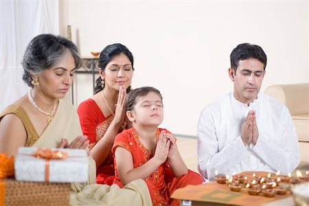 Family praying in front of figurines of God Stock Photo - Premium Royalty-Free, Code: 630-01877607