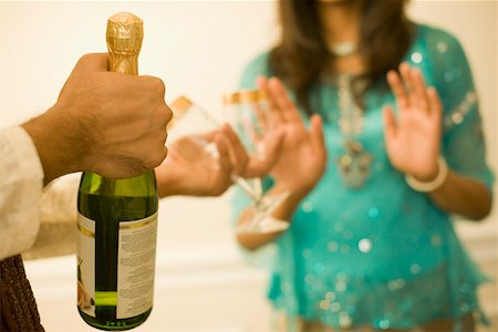 Close-up of a man's hand holding a champagne bottle Stock Photo - Premium Royalty-Free, Code: 630-01877716