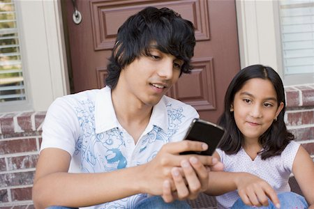 Teenage boy sitting with his sister Stock Photo - Premium Royalty-Free, Code: 630-01877773