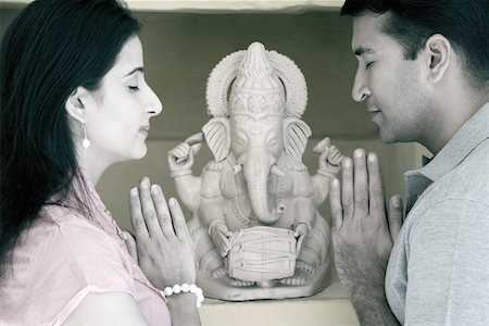 Side profile of a mid adult couple praying in front of a statue of God Ganesha Stock Photo - Premium Royalty-Free, Code: 630-01872864