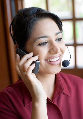 Close-up of a businesswoman wearing a headset and talking on a mobile phone and smiling Stock Photo - Premium Royalty-Free, Code: 630-01873150