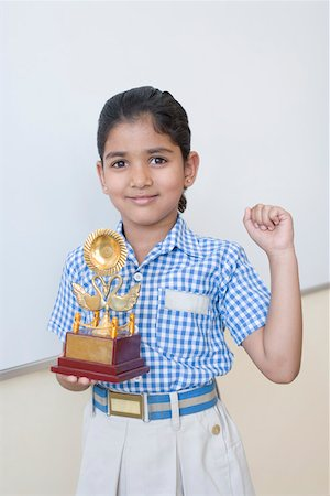 Portrait of a schoolgirl holding a trophy and smiling Stock Photo - Premium Royalty-Free, Code: 630-01873517