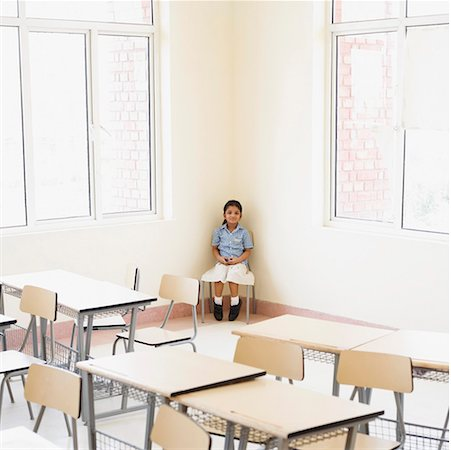 Schoolgirl sitting in the corner of a classroom Stock Photo - Premium Royalty-Free, Code: 630-01873577