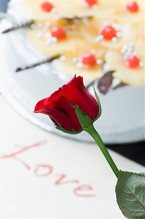 red stick candy - Close-up of a red rose near a cake with a greeting card Stock Photo - Premium Royalty-Free, Code: 630-02219907