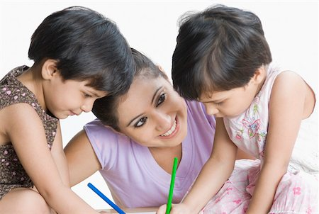 Two girls drawing in sketch pads and their mother looking at them Stock Photo - Premium Royalty-Free, Code: 630-02220053