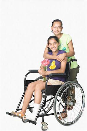 Teenage girl sitting in a wheelchair and her sister standing behind her Stock Photo - Premium Royalty-Free, Code: 630-02220259