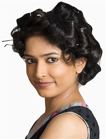 Portrait of a young woman with curlers in her hair Stock Photo - Premium Royalty-Free, Code: 630-03479384