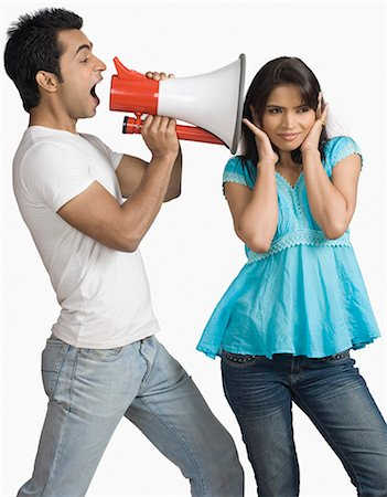 preteen girl boyfriends - Side profile of a young man blowing a bullhorn with a teenage girl covering her ears Stock Photo - Premium Royalty-Free, Code: 630-03479394