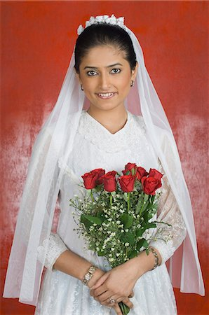Portrait of a newlywed bride holding a bouquet of flowers and smiling Stock Photo - Premium Royalty-Free, Code: 630-03479510