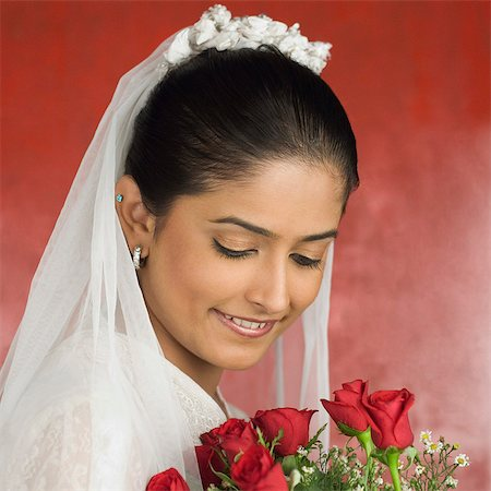 Close-up of a newlywed bride holding a bouquet of flowers and smiling Stock Photo - Premium Royalty-Free, Code: 630-03479512