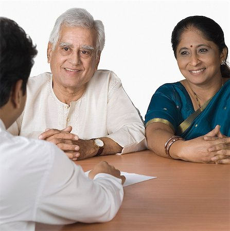 Couple discussing with a financial advisor and smiling Stock Photo - Premium Royalty-Free, Code: 630-03479739