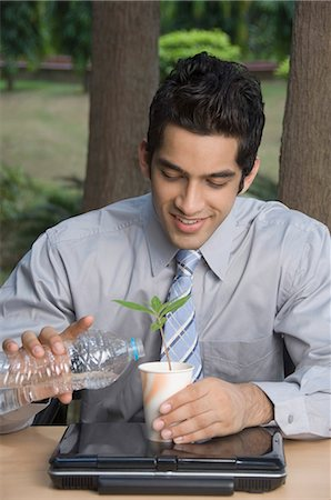 Businessman watering a plant Stock Photo - Premium Royalty-Free, Code: 630-03479867