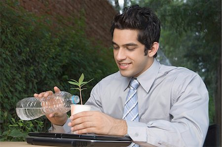 Businessman watering a plant Stock Photo - Premium Royalty-Free, Code: 630-03479868