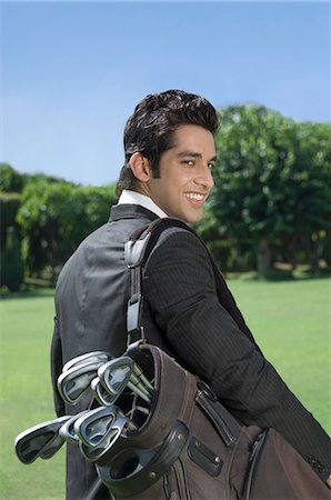 Businessman carrying a golf bag Stock Photo - Premium Royalty-Free, Code: 630-03479894