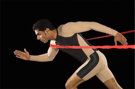 finish line - Athlete running through a finishing line Stock Photo - Premium Royalty-Free, Code: 630-03480385