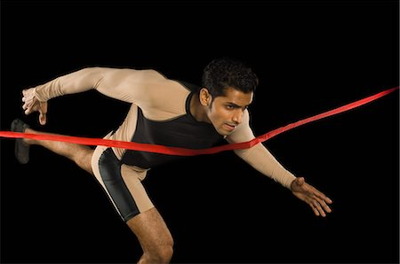 finish line - Athlete running through a finishing line Stock Photo - Premium Royalty-Free, Code: 630-03480381