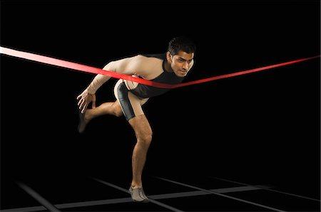 sprint - Athlete running through a finishing line Stock Photo - Premium Royalty-Free, Code: 630-03480382