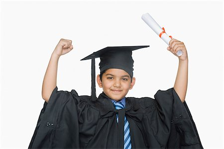 Portrait of a boy in graduation gown holding a diploma Stock Photo - Premium Royalty-Free, Code: 630-03481240