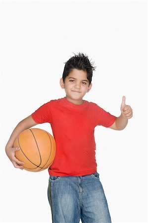 Boy holding a basketball and showing a thumbs up sign Stock Photo - Premium Royalty-Free, Code: 630-03481256