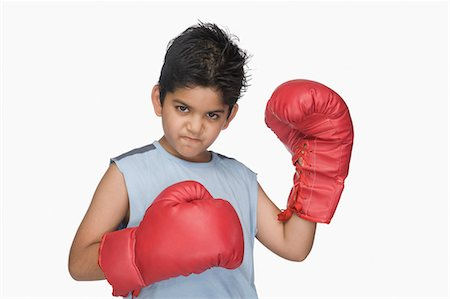 Portrait of a boy wearing boxing gloves Stock Photo - Premium Royalty-Free, Code: 630-03481265