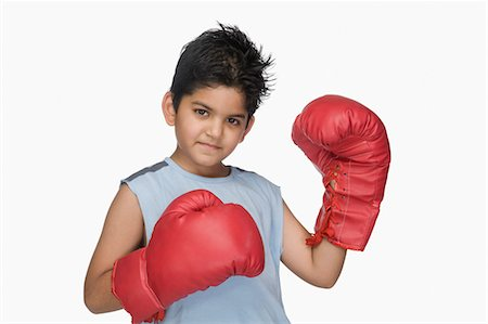 Portrait of a boy wearing boxing gloves Stock Photo - Premium Royalty-Free, Code: 630-03481266