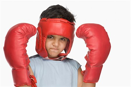 Portrait of a boy wearing boxing gloves and head protector Stock Photo - Premium Royalty-Free, Code: 630-03481267