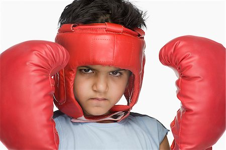Portrait of a boy wearing boxing gloves and head protector Stock Photo - Premium Royalty-Free, Code: 630-03481268