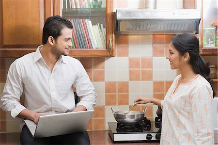 Man working on a laptop while his wife cooking in the kitchen Stock Photo - Premium Royalty-Free, Code: 630-03482596