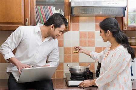 Man working on a laptop while his wife cooking in the kitchen Stock Photo - Premium Royalty-Free, Code: 630-03482597