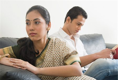 sad lovers break up - Woman looking sad with her husband reading a book Stock Photo - Premium Royalty-Free, Code: 630-03482662
