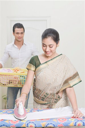 Woman ironing clothes with her husband holding a laundry basket Stock Photo - Premium Royalty-Free, Code: 630-03482683