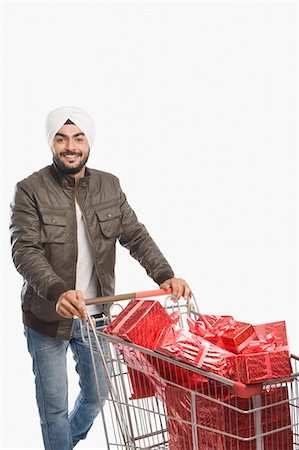 Portrait of a man pushing a shopping cart of gifts Stock Photo - Premium Royalty-Free, Code: 630-03482757