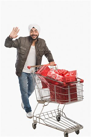 Man pushing a shopping cart of gifts Stock Photo - Premium Royalty-Free, Code: 630-03482758
