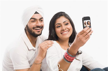 Couple taking a picture of themselves with a camera phone Stock Photo - Premium Royalty-Free, Code: 630-03482773