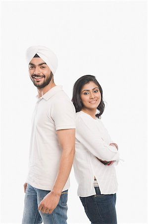 Couple standing back to back and smiling Stock Photo - Premium Royalty-Free, Code: 630-03482785