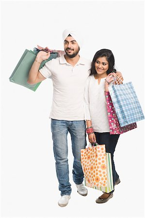 Couple carrying shopping bags and smiling Stock Photo - Premium Royalty-Free, Code: 630-03482780