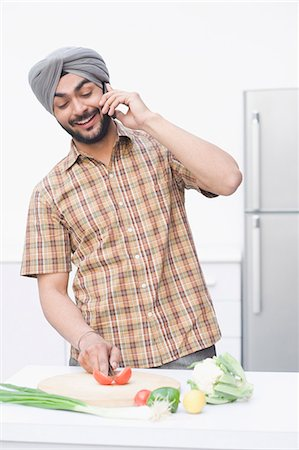 Man chopping vegetables and talking on a mobile phone Stock Photo - Premium Royalty-Free, Code: 630-03482833