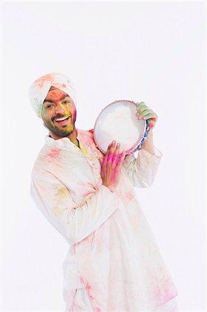 Portrait of a man playing tambourine on Holi Stock Photo - Premium Royalty-Free, Code: 630-03482910