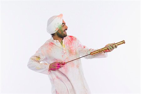 Man playing Holi with a pichkari Stock Photo - Premium Royalty-Free, Code: 630-03482913