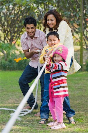 Couple with their children playing tug-of-war in a park Stock Photo - Premium Royalty-Free, Code: 630-03483087