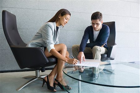 Businessman assisting businesswoman in signing document Stock Photo - Premium Royalty-Free, Code: 632-05401235