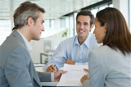 Couple discussing contract while meeting with businessman Stock Photo - Premium Royalty-Free, Code: 632-05401305