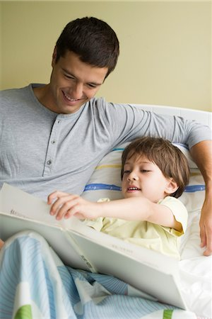 page - Father and son reading book together in bed Stock Photo - Premium Royalty-Free, Code: 632-05554075