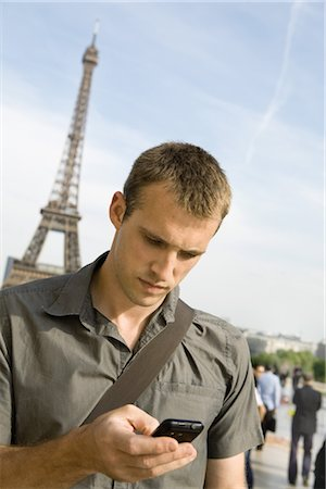 Man text messaging with cell phone, Eiffel Tower in background, Paris, France Stock Photo - Premium Royalty-Free, Code: 632-05554086