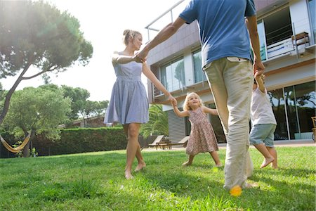 Family playing ring-around-the-rosy outdoors Stock Photo - Premium Royalty-Free, Code: 632-05554188